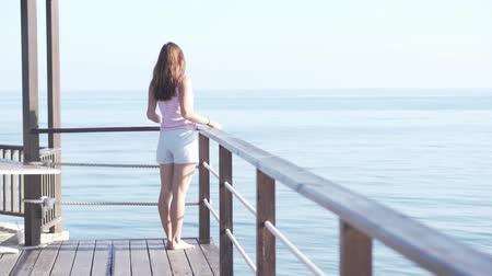 jamajka : A woman in short shorts stands on the edge of a wooden bridge. She looks at the sea, enjoys the wind, has fun