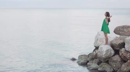 стенд : A woman is standing on rocks near the sea. She makes a deep entrance and slowly raises her hands up to the sky. She is calm and serene. Great video. Short dress, bare back