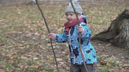 колебание : little girl on a walk in the autumn forest. The girl keeps two large sticks in her hands and dances. She is wearing a jacket, a scarf and a hat. The girl is laughing and having fun