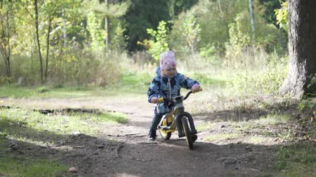 bikers : The beautiful autumn sun is shining. Little girl rides a bike ahead. The girl is wearing a jacket and hat. She slowly kicks and moves forward. Stock Footage