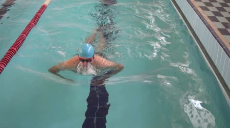 calções de banho : man swims in the pool. He is swimming breaststroke on the first track. Training in the indoor pool. On the mans blue hat and glasses