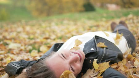 pairar : A beautiful young woman lies in yellow foliage under a tree. Yellow leaves fall on top of it. The girl smiles. On the street golden autumn. Woman laughs and closes her eyes