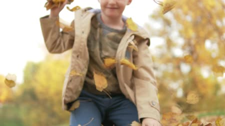 hazugság : The naughty boy throws fallen yellow leaves into the camera and laughs