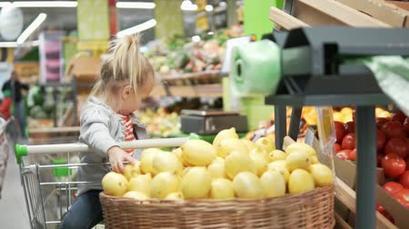 cesta : Little girl sits in the grocery cart in the supermarket. Next to the baby is a large basket with lemons. The girl takes a lemon and throws them into the basket. She is fun. Funny customer. Little mist