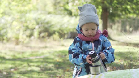 alt : A little girl pours herself tea from a thermos. The baby is standing in the forest near a fallen tree, it is autumn on the street. A girl holds in one hand a cup, in the other a thermos Filmati Stock