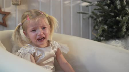necessidade : the little girl is crying. The girl has an elegant dress. She is sitting in a white armchair, not a big tree near and actively crying. In the house a holiday, New year. Baby is tired