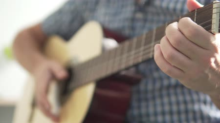 akord : A man holds a guitar. The tool is a close up, the man in the klekato ybubashka is blurred. In the frame of his hand plays guitar