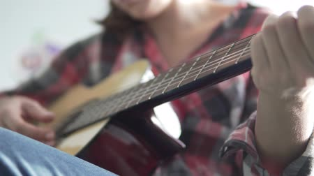 csípés : A girl in a plaid shirt learns to play the guitar. Guitar in focus. Playing guitar. Close-up of a womans guitar and hands
