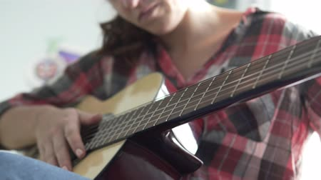 csípés : The girl in a plaid shirt plays the guitar. Guitar in focus. The girl is blurred. She touches the strings and clamps them with her fingers.
