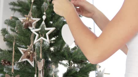 intrigue : Woman decorates the Christmas tree. She slowly hangs a wooden star on a branch. In the frame of a womans hand, a tree and a toy