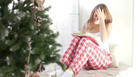 oturur : A woman in her pajamas is sitting by the window reading a book. Nearby is a Christmas tree. Outside the frost. The girl turns the pages in the book and looks at the Christmas tree. Morning christmas