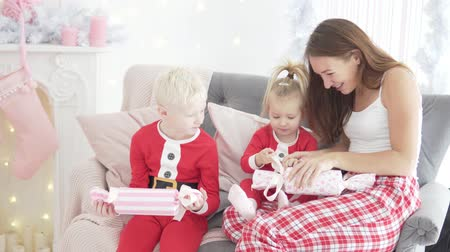 goes : Mom and her children open Christmas presents. The family is sitting on the couch by the Christmas fireplace. All are wearing red pajamas. The room is bright and beautiful.
