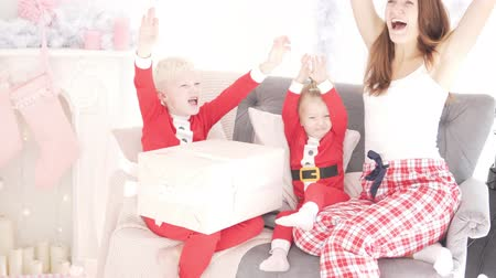 gives : Mom and kids are enjoying Christmas. They raise their hands up and shout joyfully. Sit on the couch in a beautiful pink living room with fireplace. New Year 2019 Stock Footage