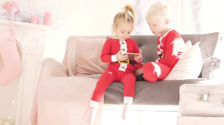 pizsama : Children sit at home on the couch and look at the phone mulch. The room is elegantly decorated for Christmas. Brother and sister in the costumes of Santa Claus. Their mother approaches the children