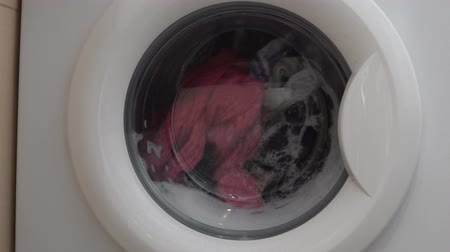 front door : the operation of the washing machine. There is a wash of colored linen. Close-up of clothes in the washing machine. Dirty water flows to the bottom. Stock Footage