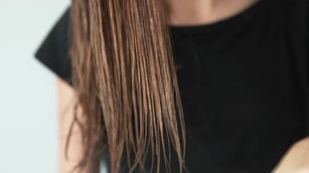 escovação : A woman slowly combing wet hair with a large hair straightening comb. The colored teeth look beautiful in the hair. Correct comb