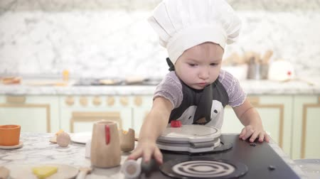 área de trabalho : Mama is wearing an apron with a penguin on a little girl. The little girl has a big white cook cap on her head. Stylish childrens wooden kitchen. Baby cooks toy food
