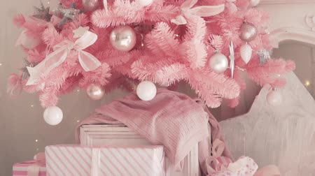 bola de fogo : Stylish beautiful Christmas tree. Dressed up as a designer. The tree is pink, flashlights flash. Under the tree are gifts. wrapped in pink packaging and tied with beautiful bows
