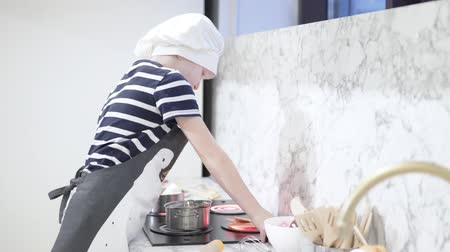 deha : A handsome and funny boy plays cooks in a toy kitchen. on the child is wearing a white chef hat and an apron. The game of future professions. Comprehensive development of children Stok Video
