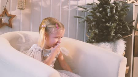 kükreme : Little girl crying at the new year tree. A child in a smart dress sits in an armchair and roars, she is given a gift, he throws it away. Tears flow down her cheeks. Christmas Stok Video