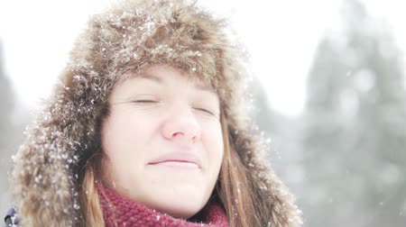 without face : A young woman in a warm winter hat with earflaps looks at the falling snow. Close-up, slow motion. Siberian frosts and warm clothes in winter.