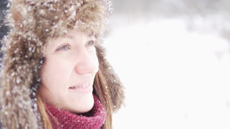 pletený : A young woman stands on the street and looks at the sky, snow flies into her face. Close-up of a girl in a warm fur hat. She smiles at the snow, closes her eyes and dreams. Cold winter