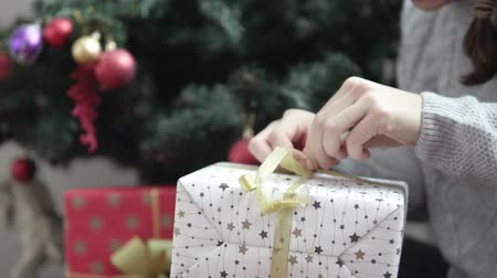 çok güzel : a woman opens a packaged New Years gift. He hardly unties the golden bow on the gift. She is not very good at unleashing it. Close-up of the box. white packaging with asterisks
