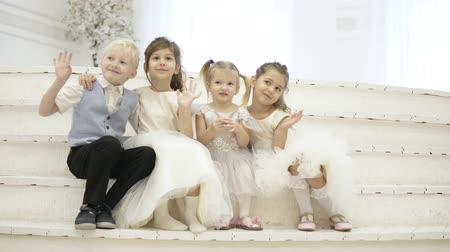 their : Elegant children sit on white wooden steps, smile and wave to the photographer. Three girls and one boy for the holidays. The guys hug each other and laugh. In the center sits a little girl. wedding Stock Footage