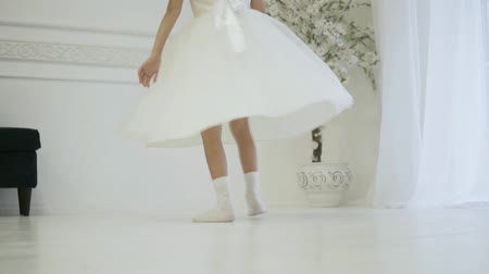 desenvolver : A girl in an elegant white dress whirl in dance. Her dress is developing. beautiful look, thin legs. White dress and socks. Little ballerina at a wedding