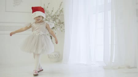télen : Little funny girl is waiting for a meeting with Santa Claus. She is dressed in an elegant dress and Christmas hat. A beautiful baby is running around in circles. she prepared a dance for Santa Claus. Stock mozgókép