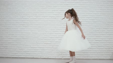 носок : beautiful girl dancing in a chic white dress. The girl is spinning, her dress is developing from the movement. Beautiful video of a little bridesmaid at a wedding Стоковые видеозаписи