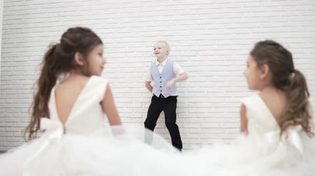 поясница : A handsome blond boy is standing by a white brick wall and telling something. The boy is dressed in a business suit. Nearby on the floor with their backs to the camera, two beautiful smart girls are s