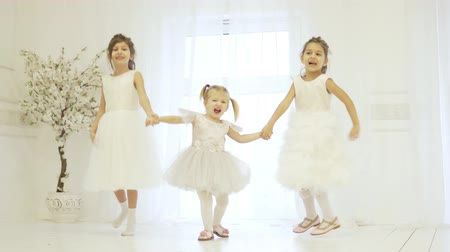 friendship dance : Three beautiful little girls are holding hands and dancing on the stage. Children are dressed in lush long dresses, they look like little brides or ballerinas. Girls hold hands and bounce up. Stylish Stock Footage