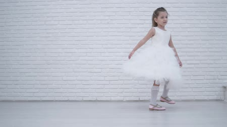 подвенечное платье : Little beautiful girl is spinning in front of photographers at the holiday. The child is wearing a fluffy white dress. She spins like a ballerina in front of the guests. cute baby at the wedding.
