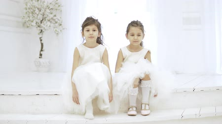 Two beautiful smart girls are sitting on the stairs and stamping their feet. The little sisters are dressed in white fluffy dresses, they are smiling cute