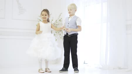 Loving couple of children. a boy and a girl are standing in a large bright room, children are smart. He hugs her and kisses her friends hand. The first love. Valentines Day