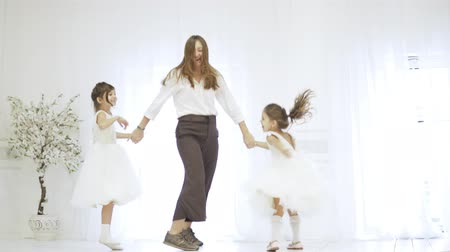 Mom and her daughters hold hands and jump on the stage. They have fun, they dance together. Girls in white elegant dresses, mother in a shirt and trousers. Preparing for the school ball