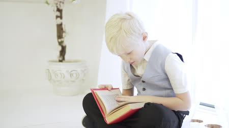 An elegant albino boy sits cross-legged on the floor and reads a thick book with small text. The child is keen on reading a fairy tale. Cute little genius