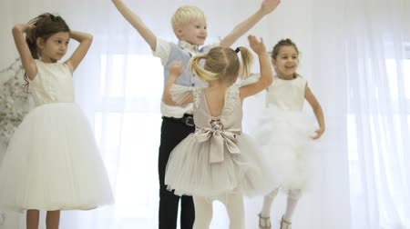 Beautiful children in elegant dresses jump on the stage, waving their hands together and dancing. Cheerful boy and three joyful sisters are having fun on holiday Stock Footage