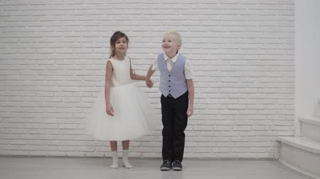 An elegant couple of children holding hands, smiling, and at the end of the video a boy hugging his young girlfriend. Children in love at the wedding. Photo session on Valentines Day Stock Footage