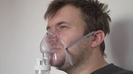 Brutal man makes an inhalation in the hospital. He has a silicone mask on his face and he breathes in pairs of medication. Close-up. The man has stubble on his face Stock Footage