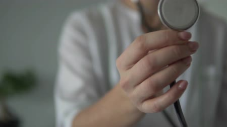 A female hand holds a stethoscope close to the camera. Close-up of the device for listening to the lungs and heart. Then picks up the phone closer to you.