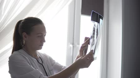 A female doctor stands by the window and examines an x-ray of the lungs. She sees the inflammation of the right lung from below, shows it. The doctor is wearing a white coat, she has a stethoscope