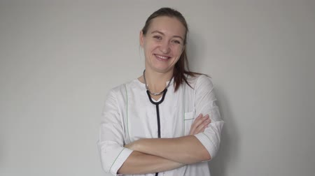 Female doctor smiling at camera at hospital. She is wearing a white coat, a stethoscope around her neck. Doctor crosses arms over chest Stock Footage