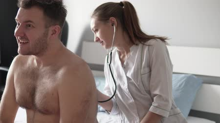 Beautiful doctor in a white coat listening to a stethoscope of a sick man. The patient is sitting on the bed, with a bare back and a woman in a white coat carefully listens to his wheezing in his lung Dostupné videozáznamy