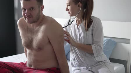 Beautiful doctor puts on a stethoscope and listens to the patients breath in the ward. A full man with a naked chest looks healthy. A woman is wearing a white robe, she is smiling sweetly Stock Footage