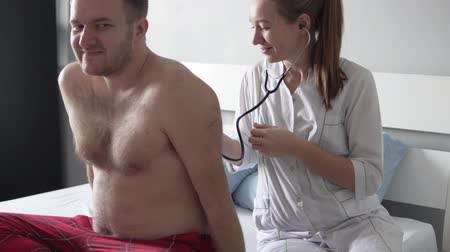Female doctor during examination of a sexy male patient, starts stroking his back and smiling coquettishly