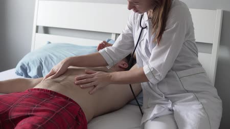 young female doctor seduces a male patient with a bare-chested. Sexy woman in white coat strokes his hairy chest Stock Footage