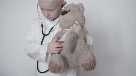 A child in a white coat plays a doctor. He listens to a teddy bear stethoscope. Cute video, the choice of the profession of the child doctor