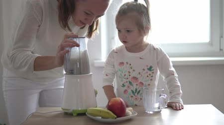Mom and little daughter are preparing a milkshake. They take the ingredients to the blender. A woman teaches her daughter to cook healthy and natural food at home.
